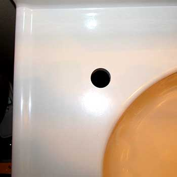 hole cut into a cultured marble bathroom sink vanity