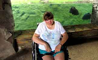 Amanda Putman McBay sitting in front of a fish exhibit