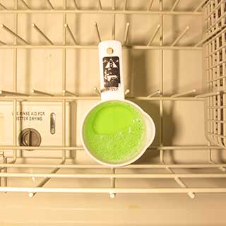container of CLR in bottom dishwasher rack