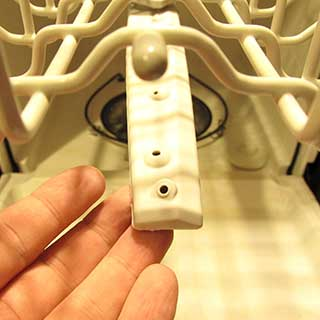inspecting the holes in a dishwasher spray arm